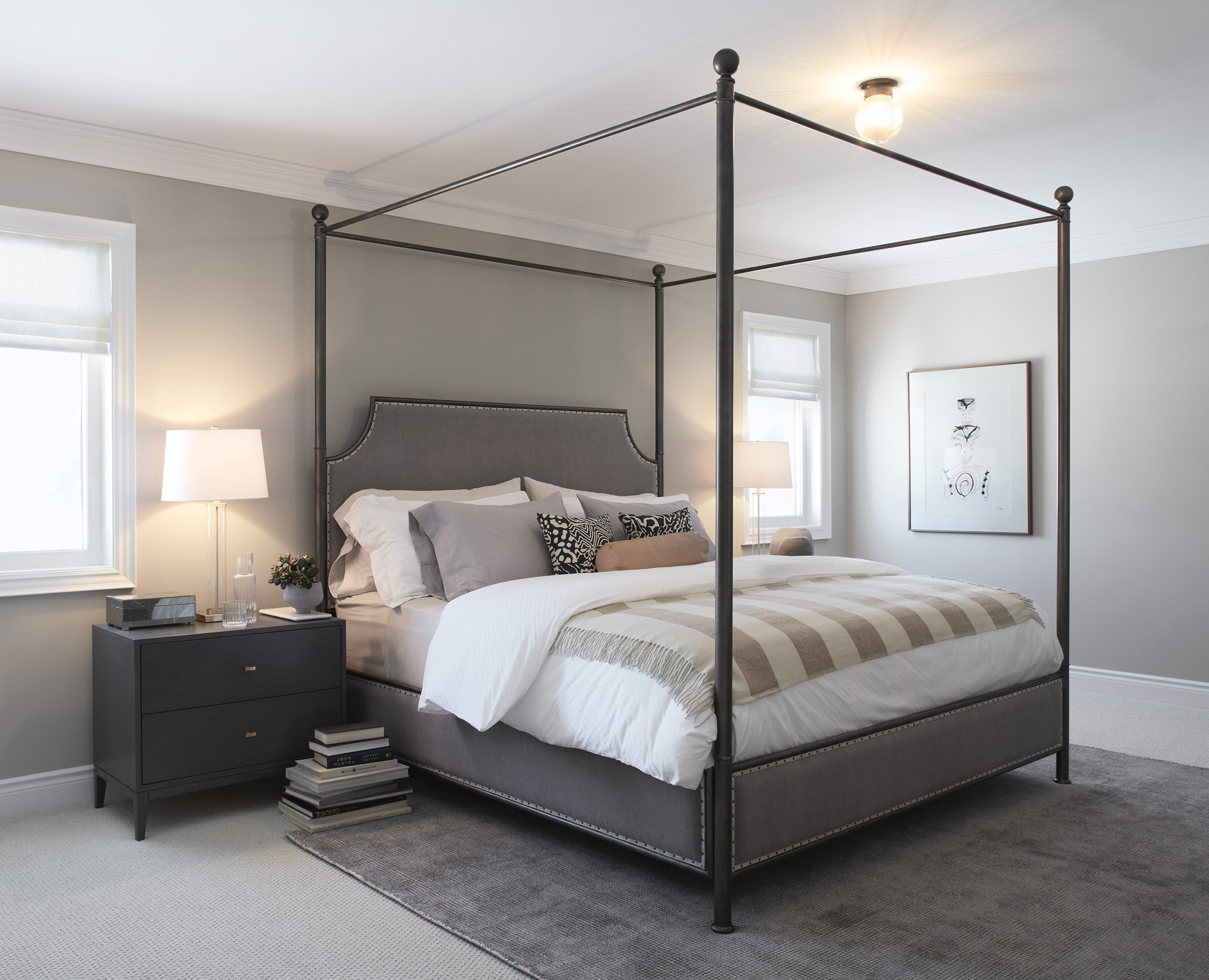 Manor Estate master bedroom with four poster bed, neutral bedding, and grey rug