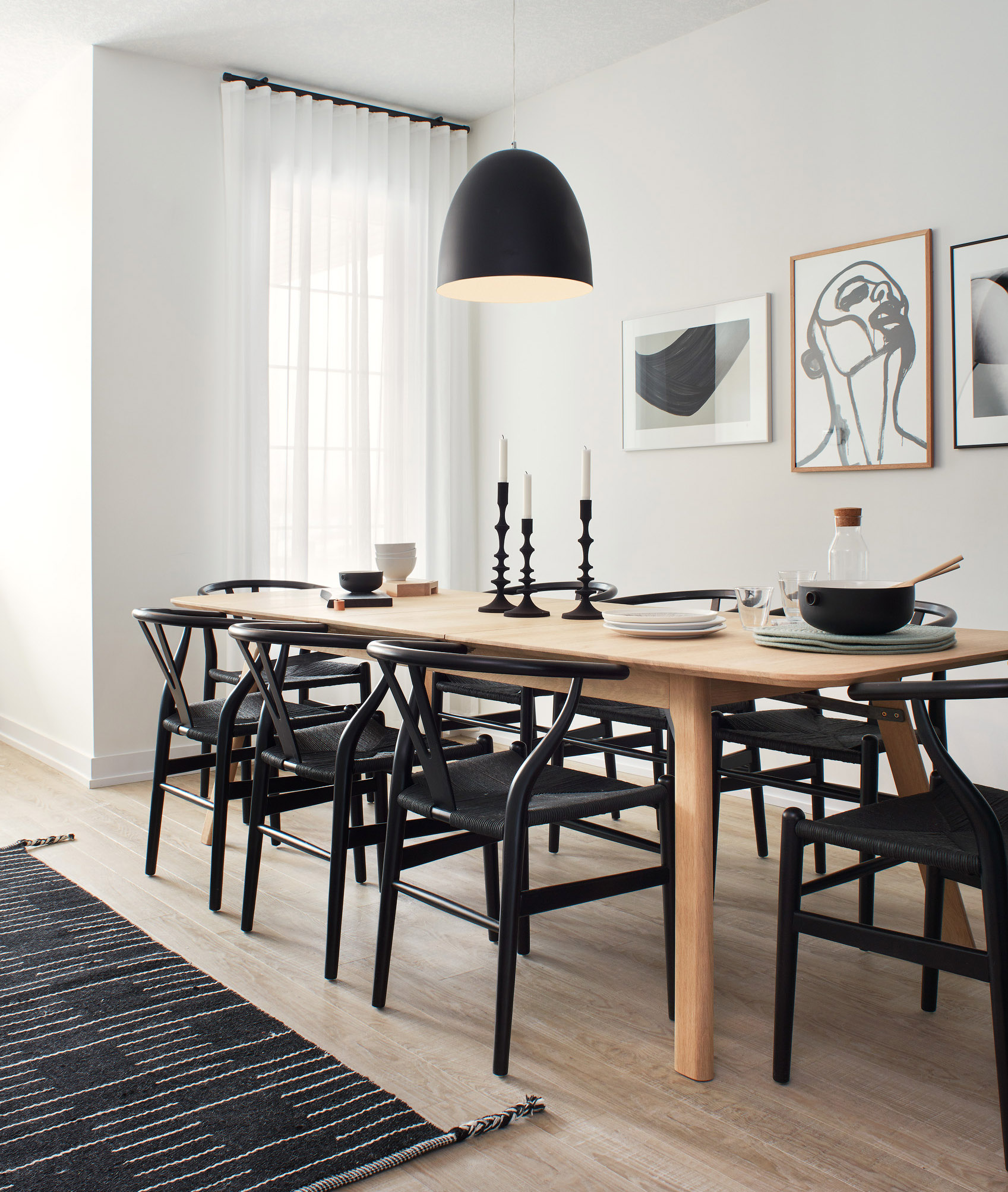 Modern Scandi dining room with wood table, black chairs, and white walls with modern artwork