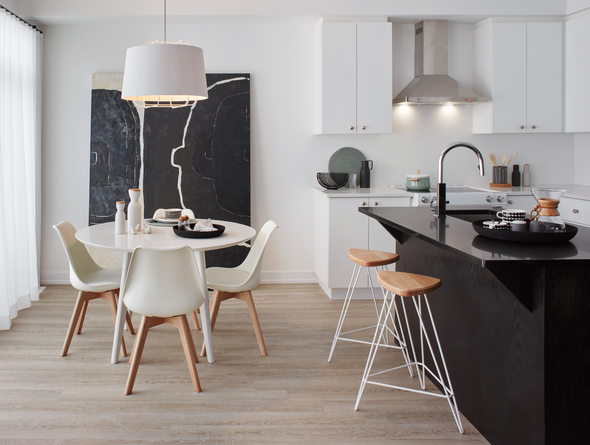 Modern Scandi with white walls, black island, and large scale black artwork