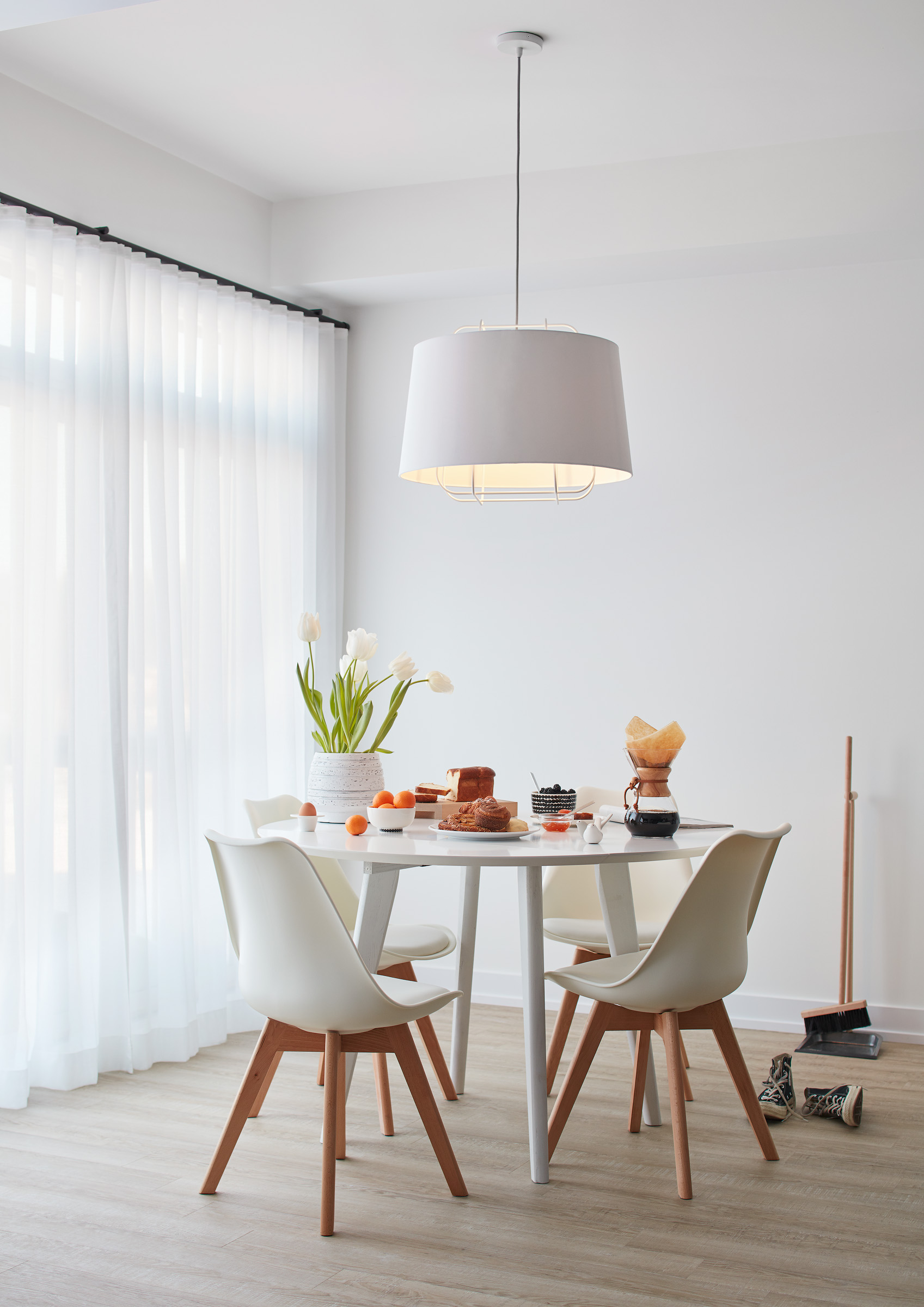 Modern Scandi breakfast area with white walls, white furniture, and table set with breakfast foods