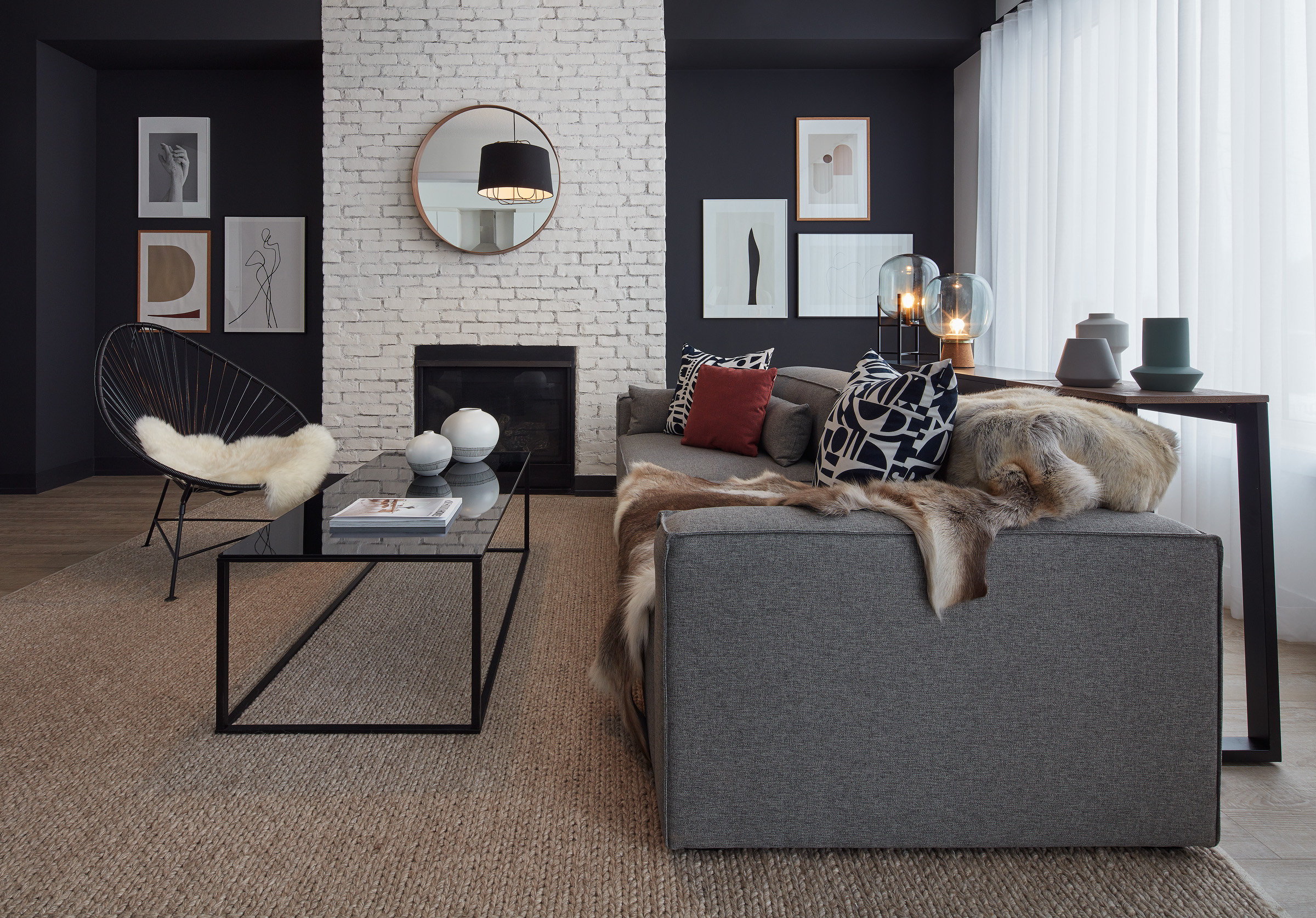 Modern Scandi living room with black and white walls, grey sofa, and fur accessories