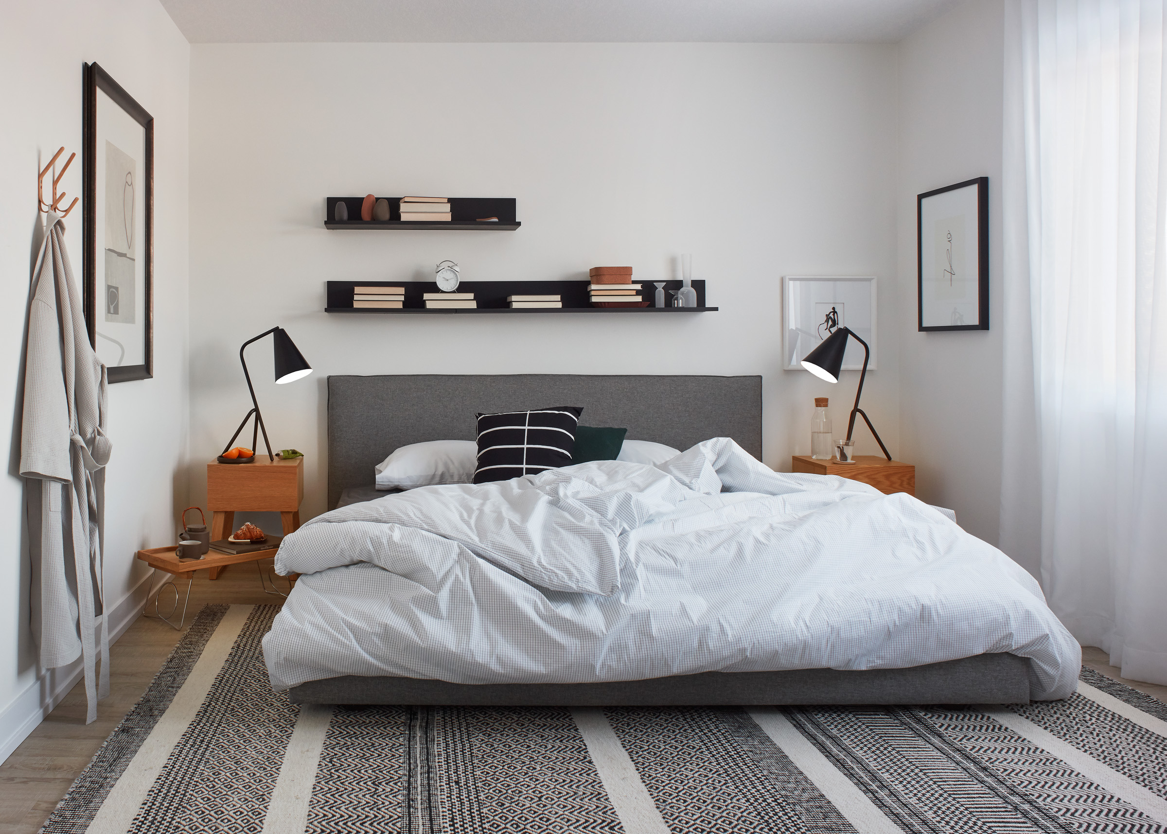 Modern Scandi bedroom with black and white colour scheme and artfully messy bed