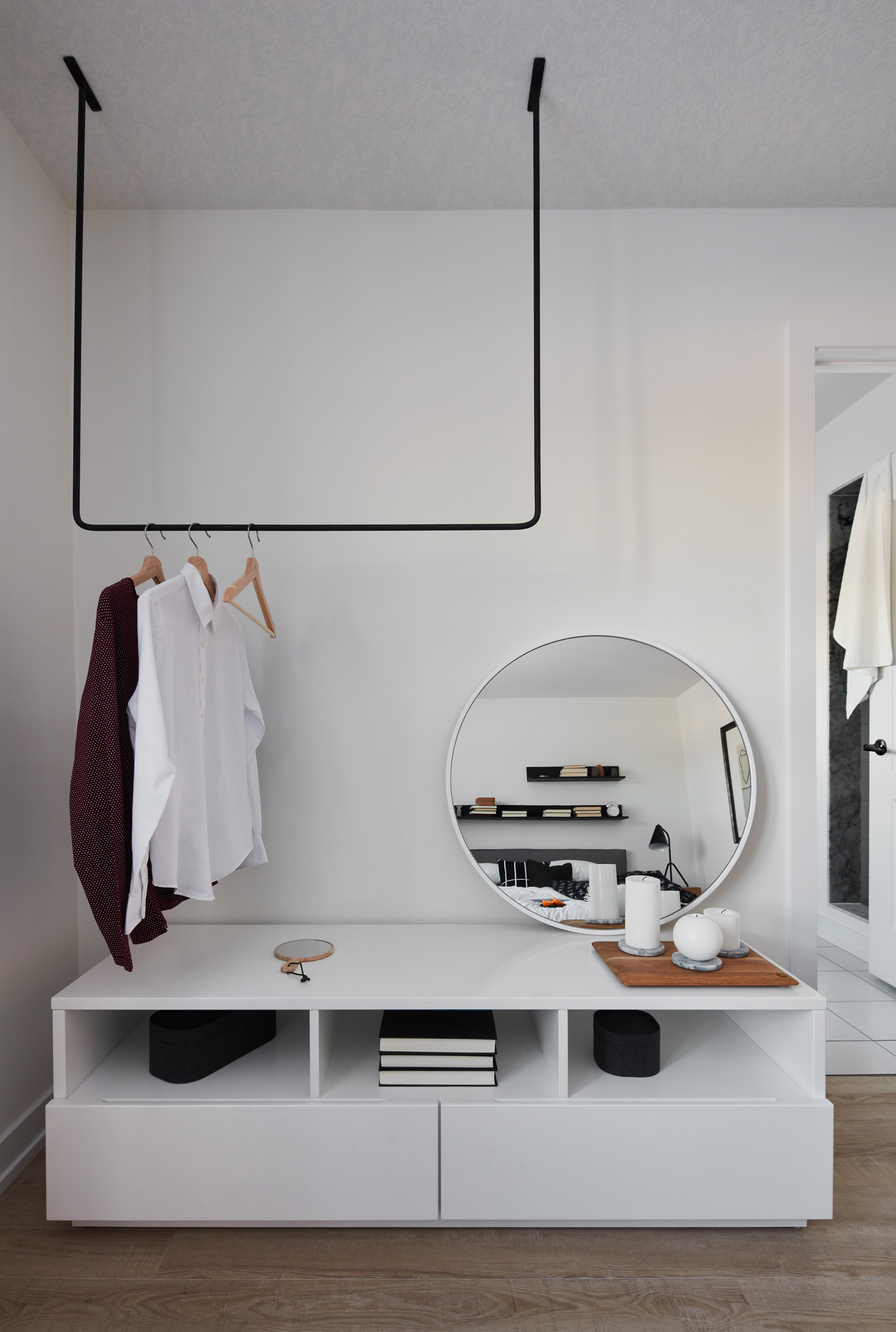 Modern Scandi bedroom, white wall with white shelving, and contemporary black metal ceiling rack