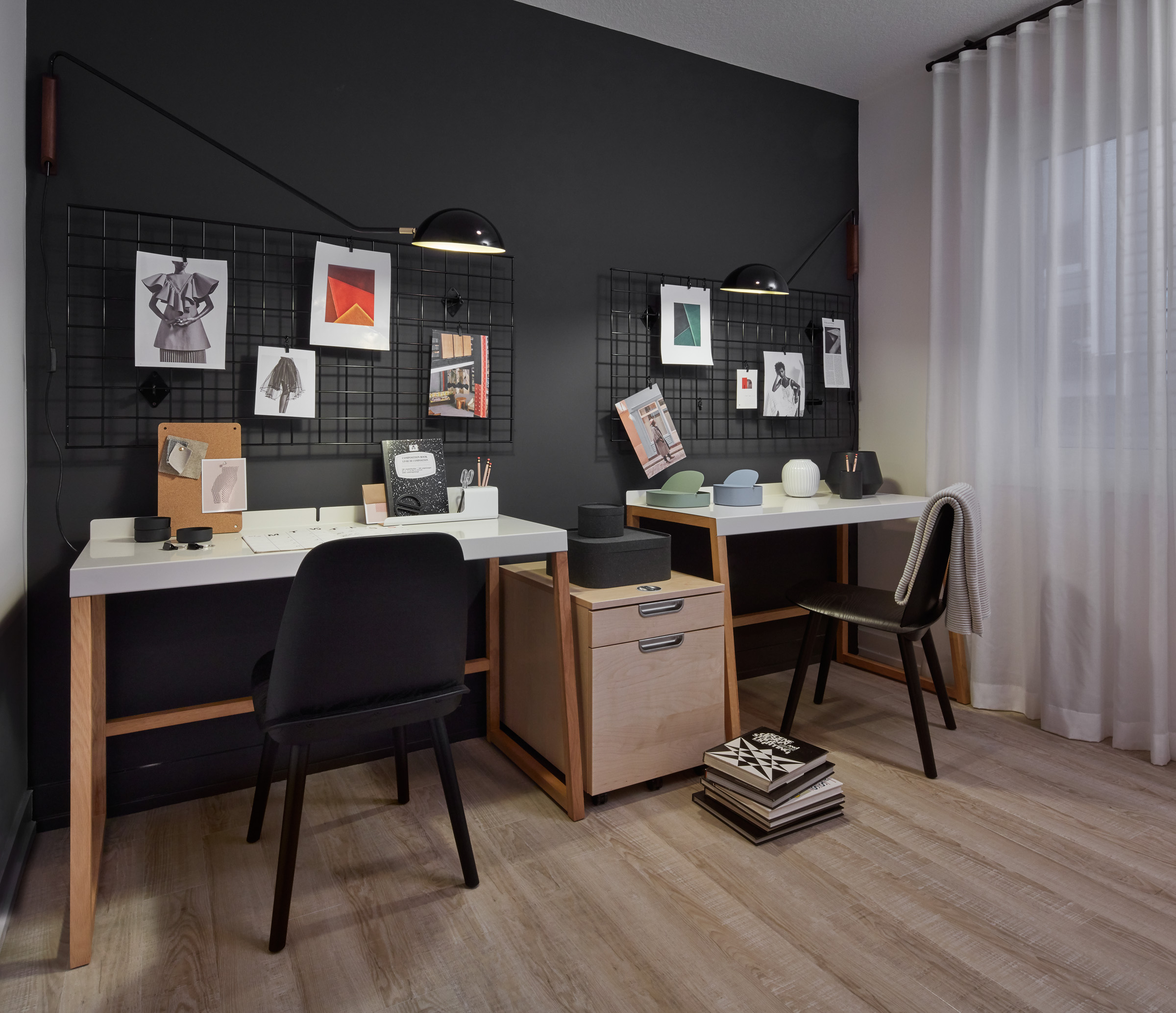 Modern Scandi workspace with two desks, black walls, and art boards on walls