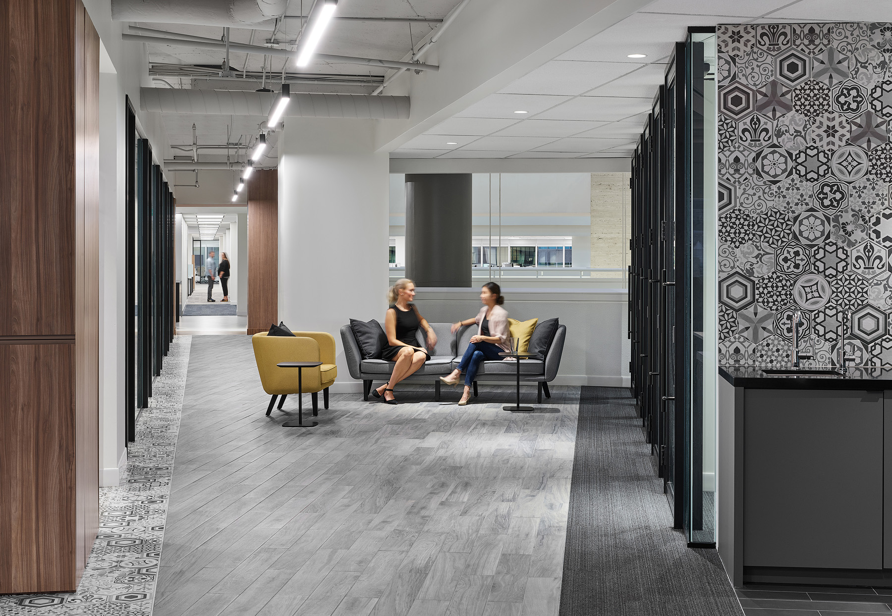 Optimus Toronto seating area with grey wood floors, patterned wall tile, and yellow and grey chairs