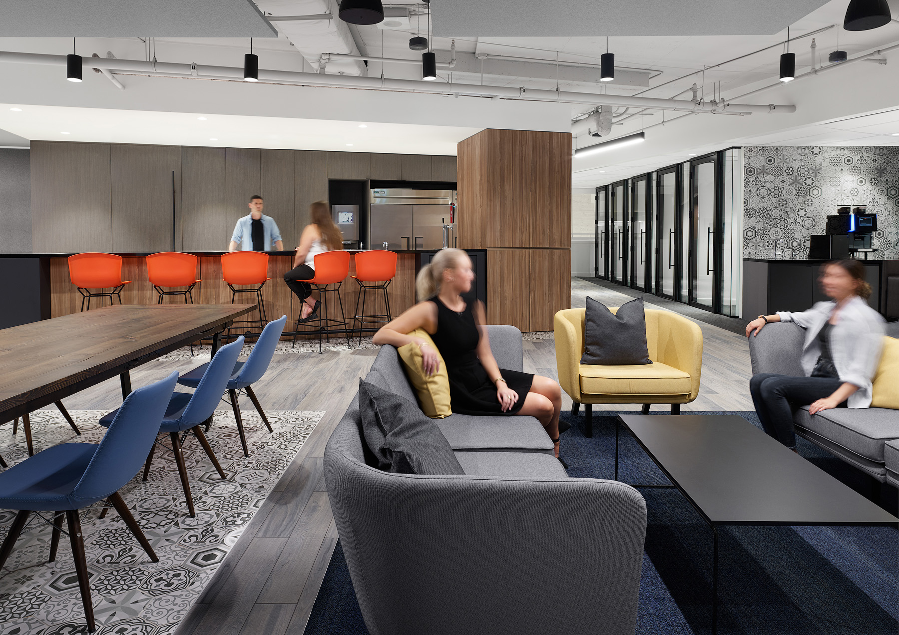 Optimus Toronto lunchroom with wood tables, patterned floor tiles, and orange, yellow, and blue chairs