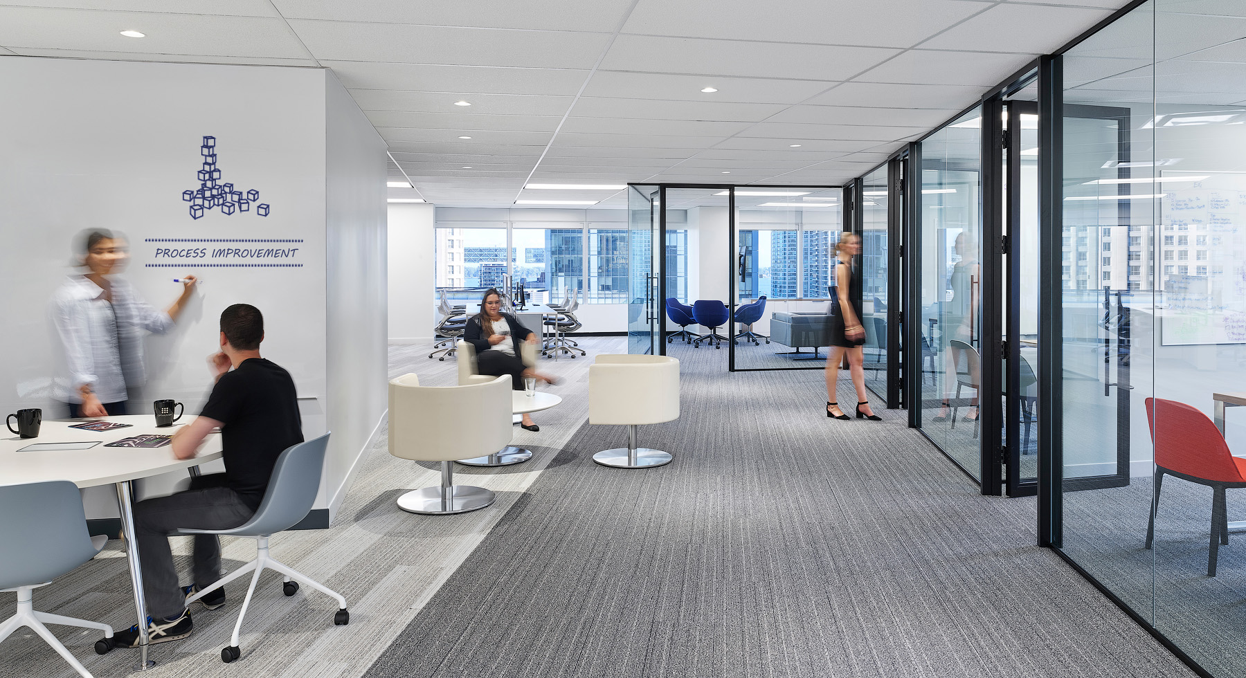 Optimus Toronto collaboration space with glass walls, various furniture, and whiteboard walls