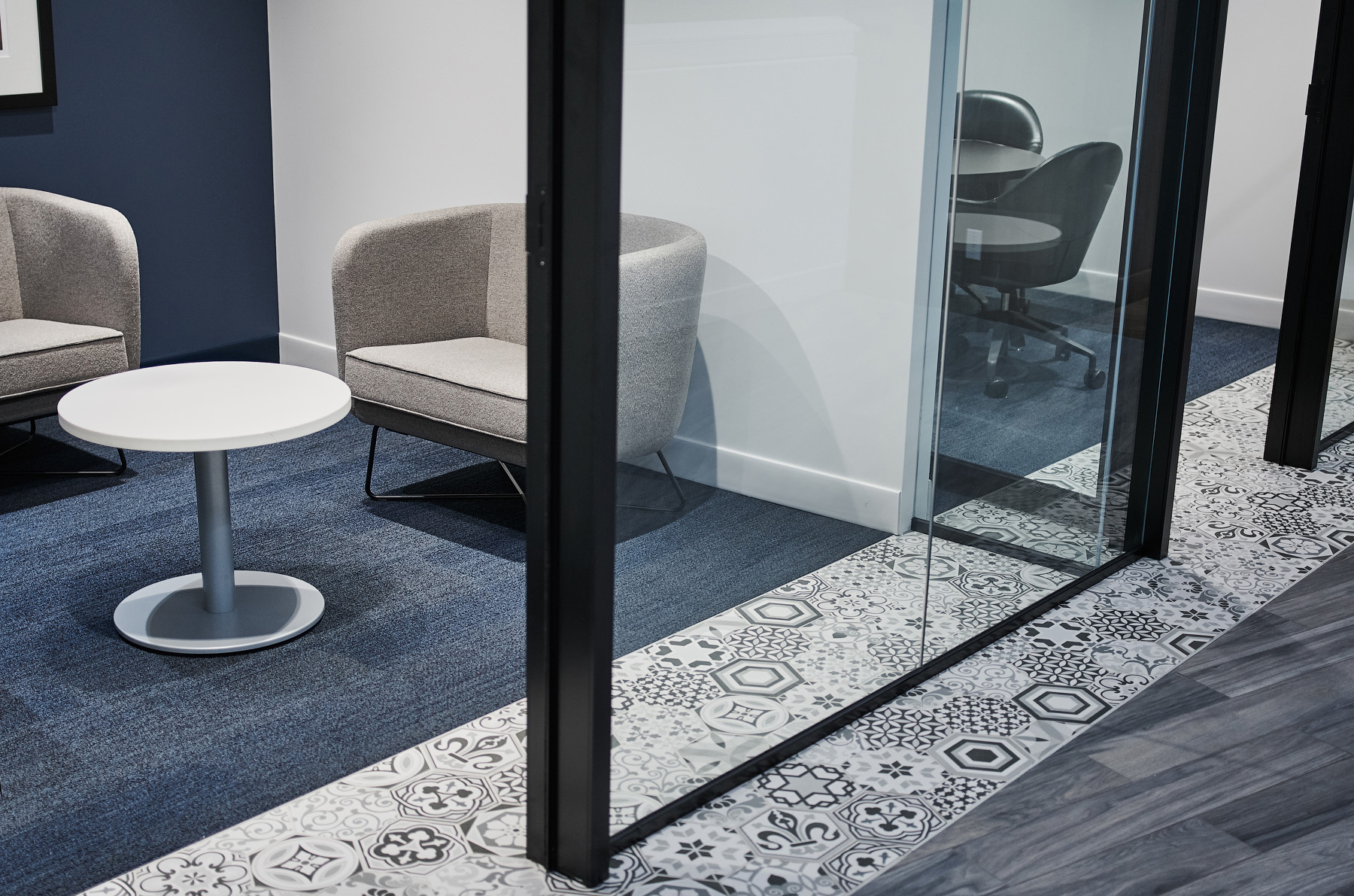 Optimus Toronto meeting room detail with glass wall, navy blue carpet, patterned floor tile, and grey upholstery