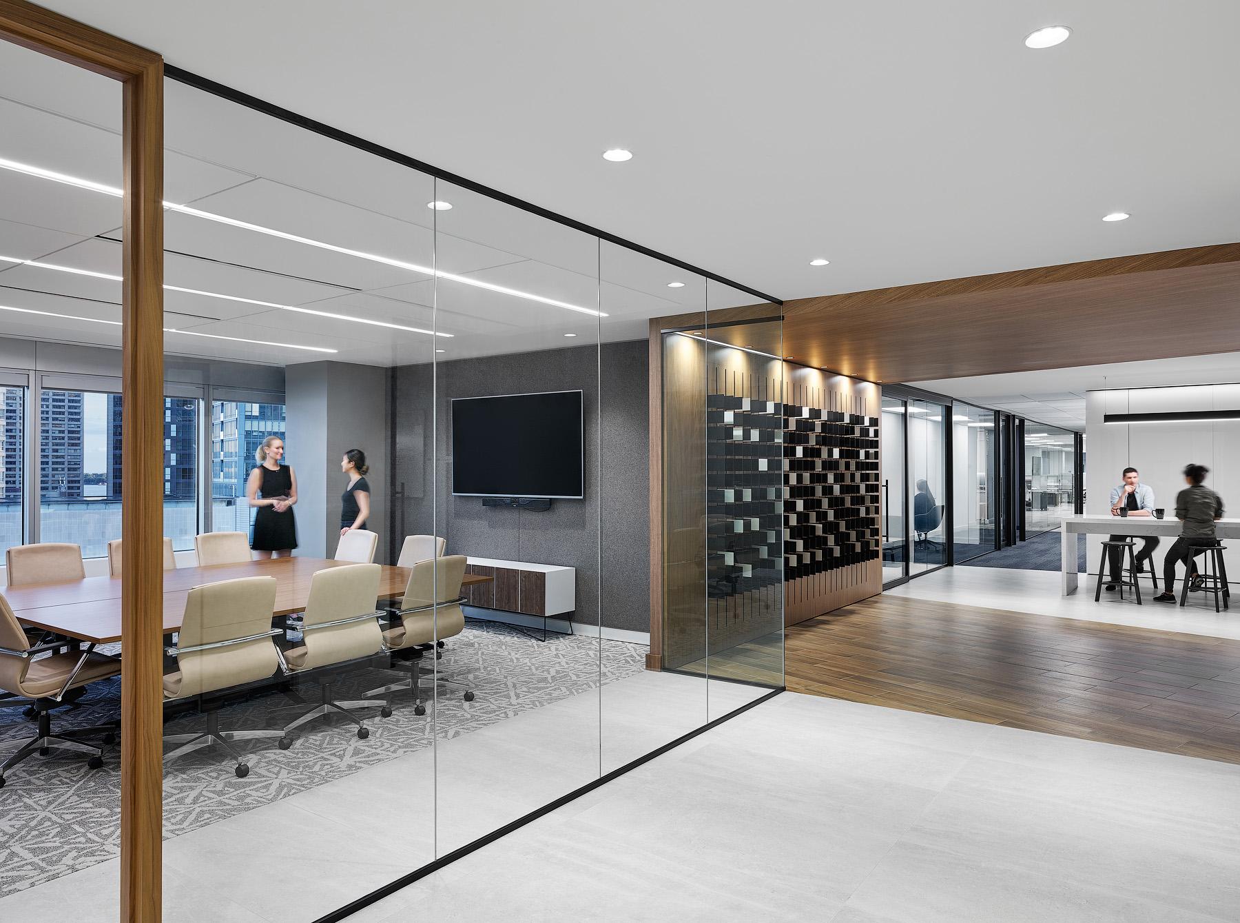 Optimus Toronto meeting room with glass walls, black metal trim, and wood paneling