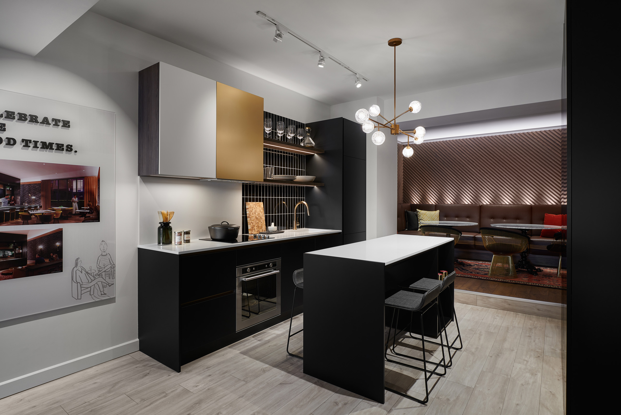 The Poet kitchen with black cabinets, light oak flooring, and gold accents
