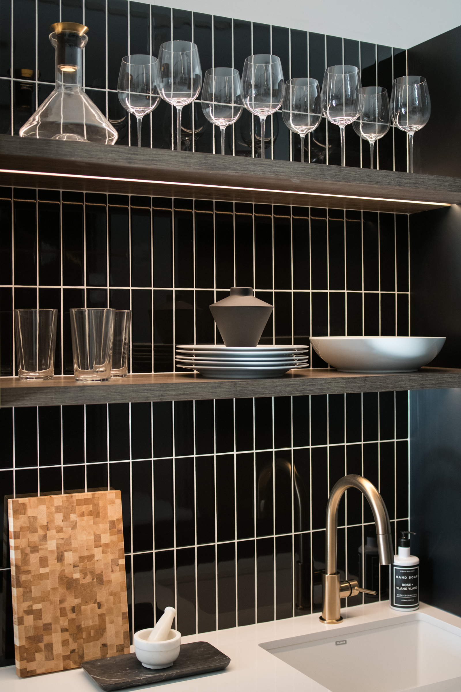The Poet kitchen shelving with black subway tile backsplash and gold faucet