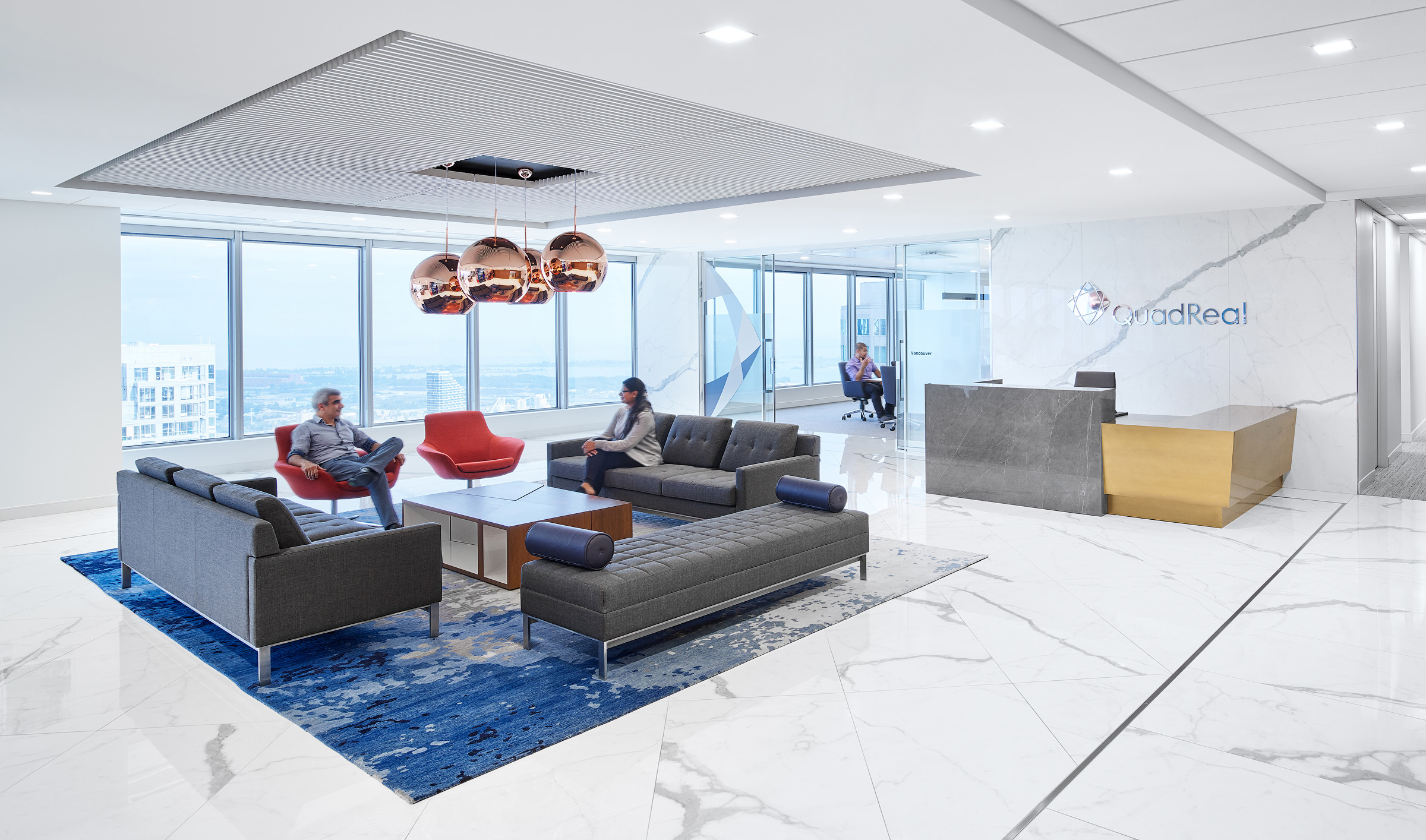 QuadReal reception with white marble floors and walls, large windows, brass desk, and seating area with grey sofas and blue rug