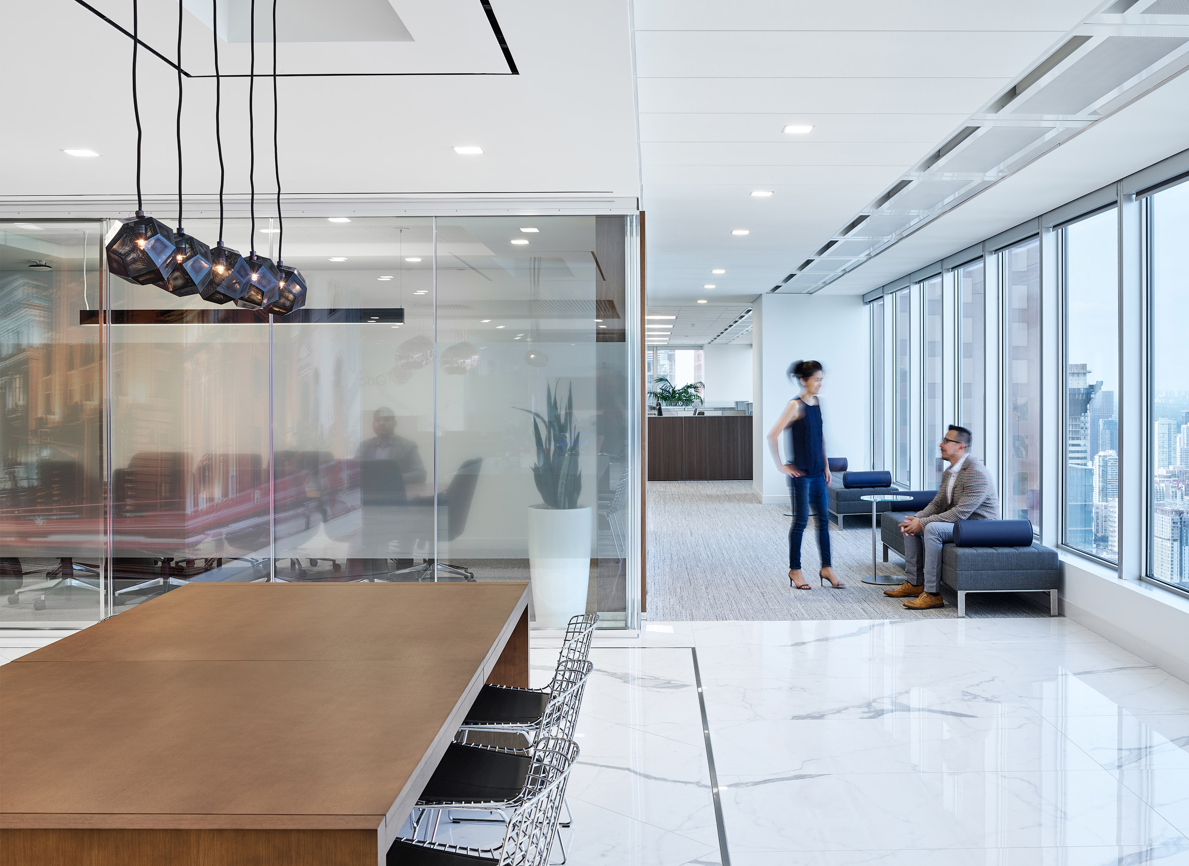 QuadReal collaboration zone with wood table, marble floors, black metal pendant lights, and large windows