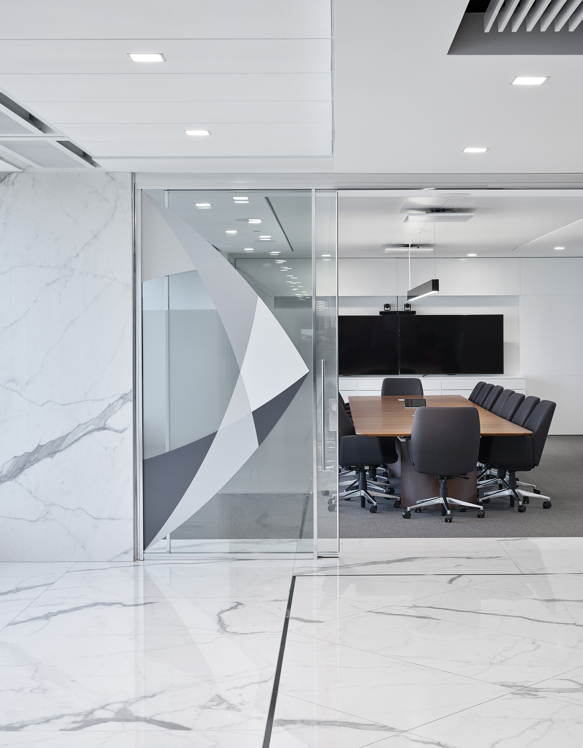 QuadReal view into meeting room with wood table through glass door with geometric pattern. Marble walls and floors outside.