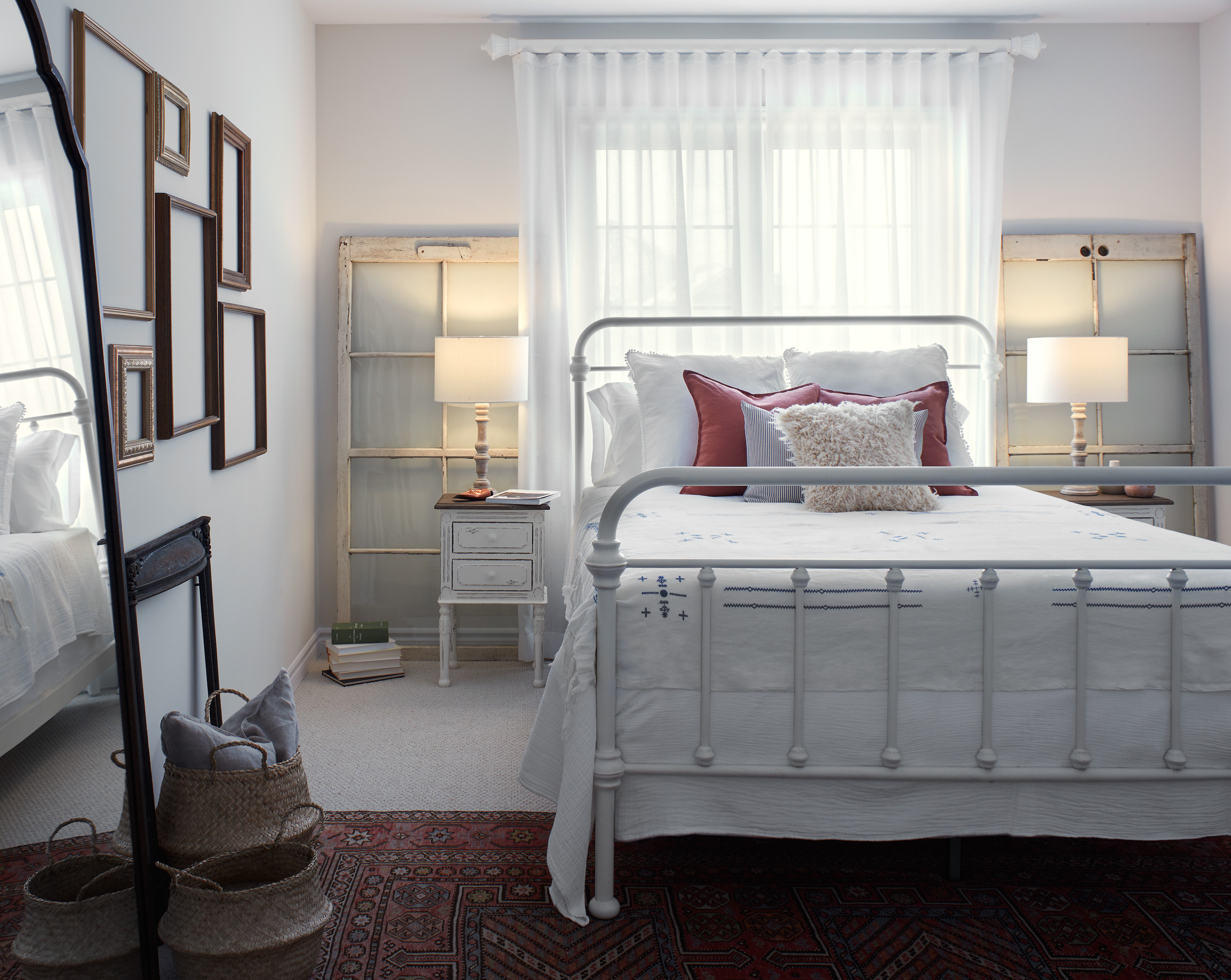 Shabby Chic bedroom with white metal bed, white bedding, and gallery wall with decorative frames
