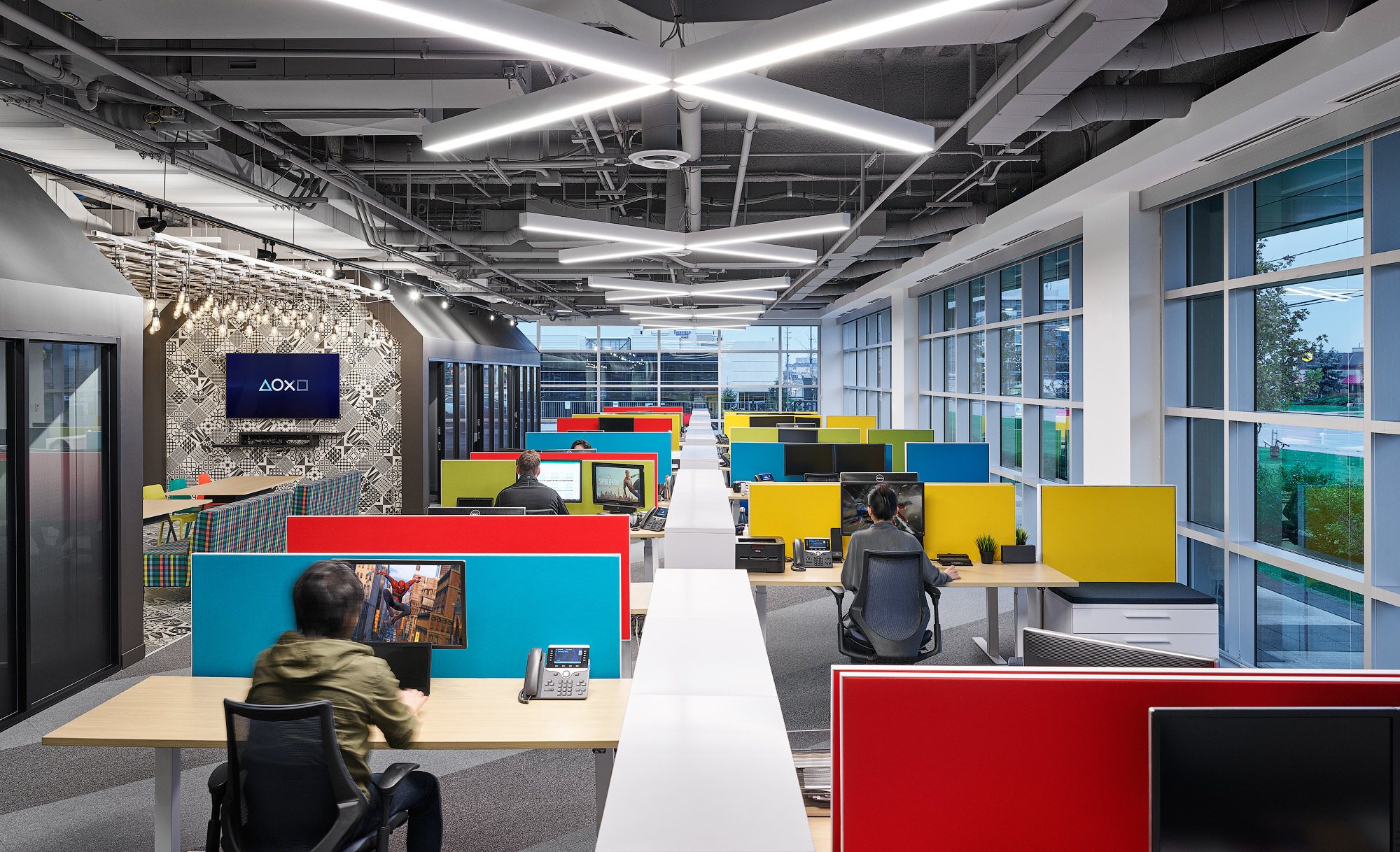 Sony SIE Toronto office. Workstations with red, blue, and yellow partitions next to large window wall