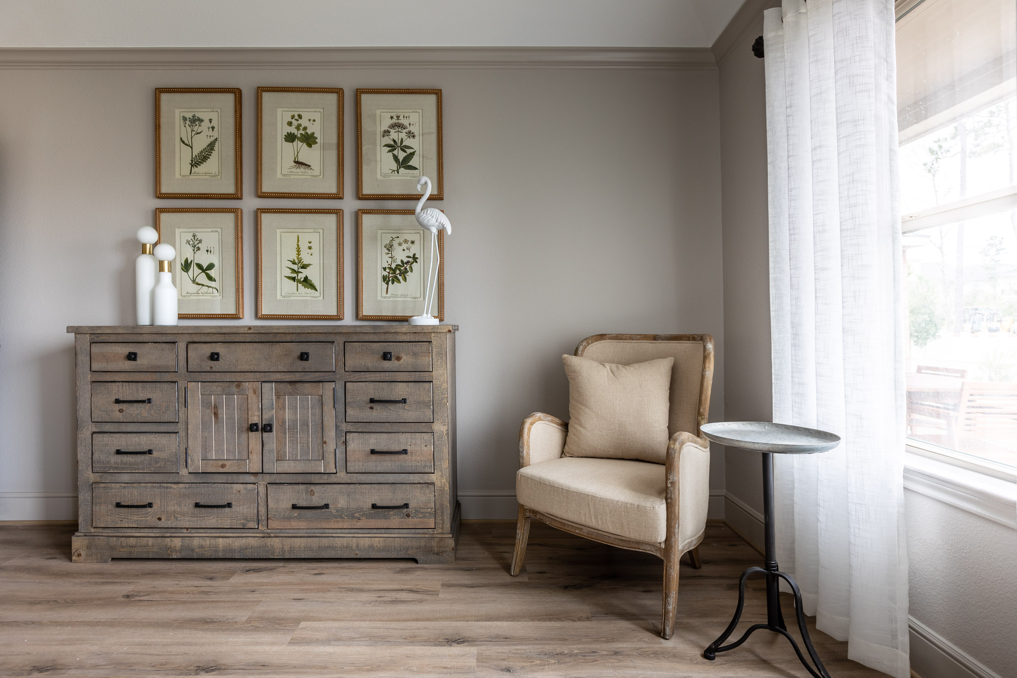 Harper's Preserve bedroom corner with traditional distressed wood dresser and linen and wood armchair