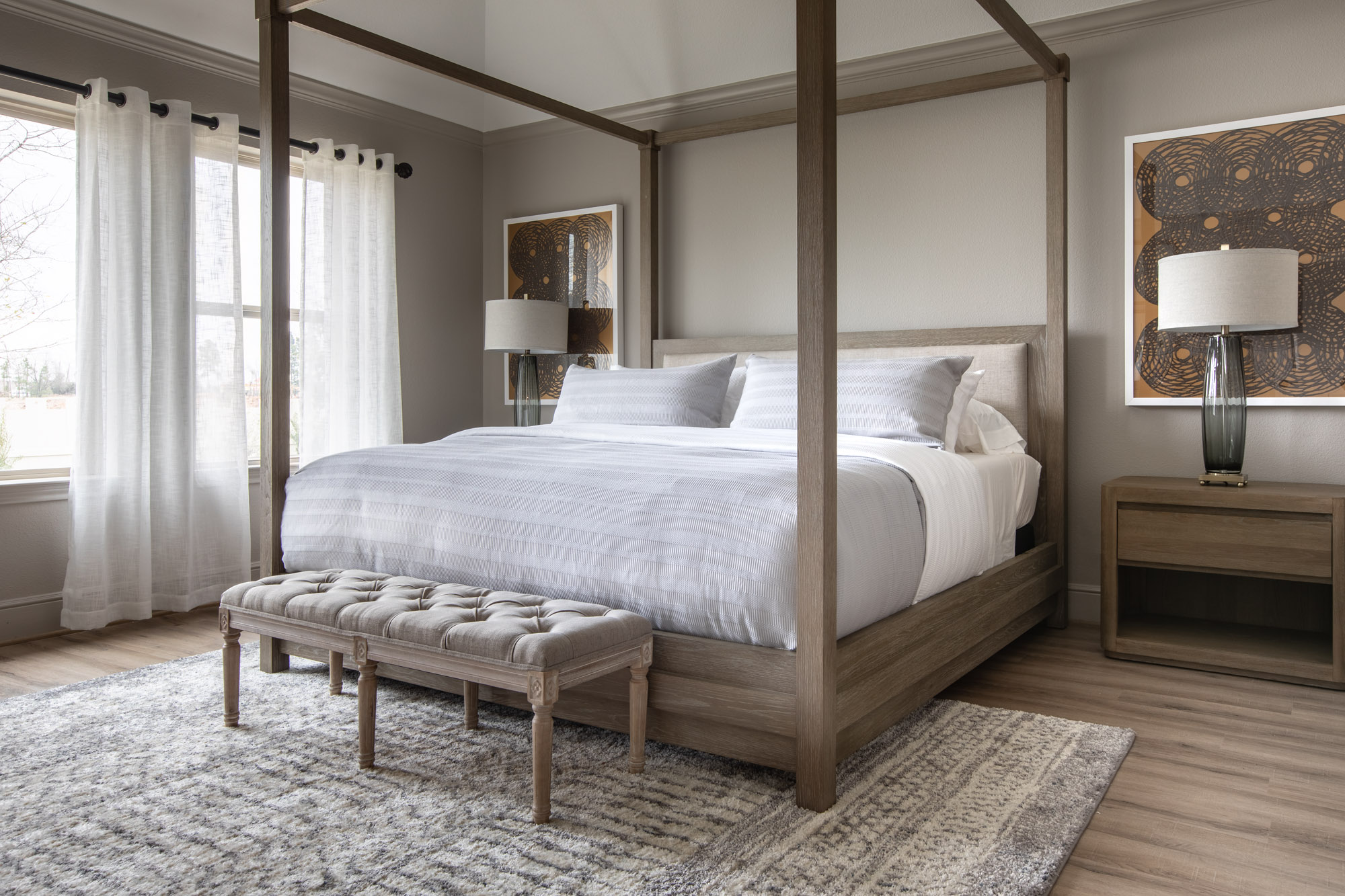 Harper's Preserve master bedroom with large wood four poster bed, light wood furniture, and patterned grey rug