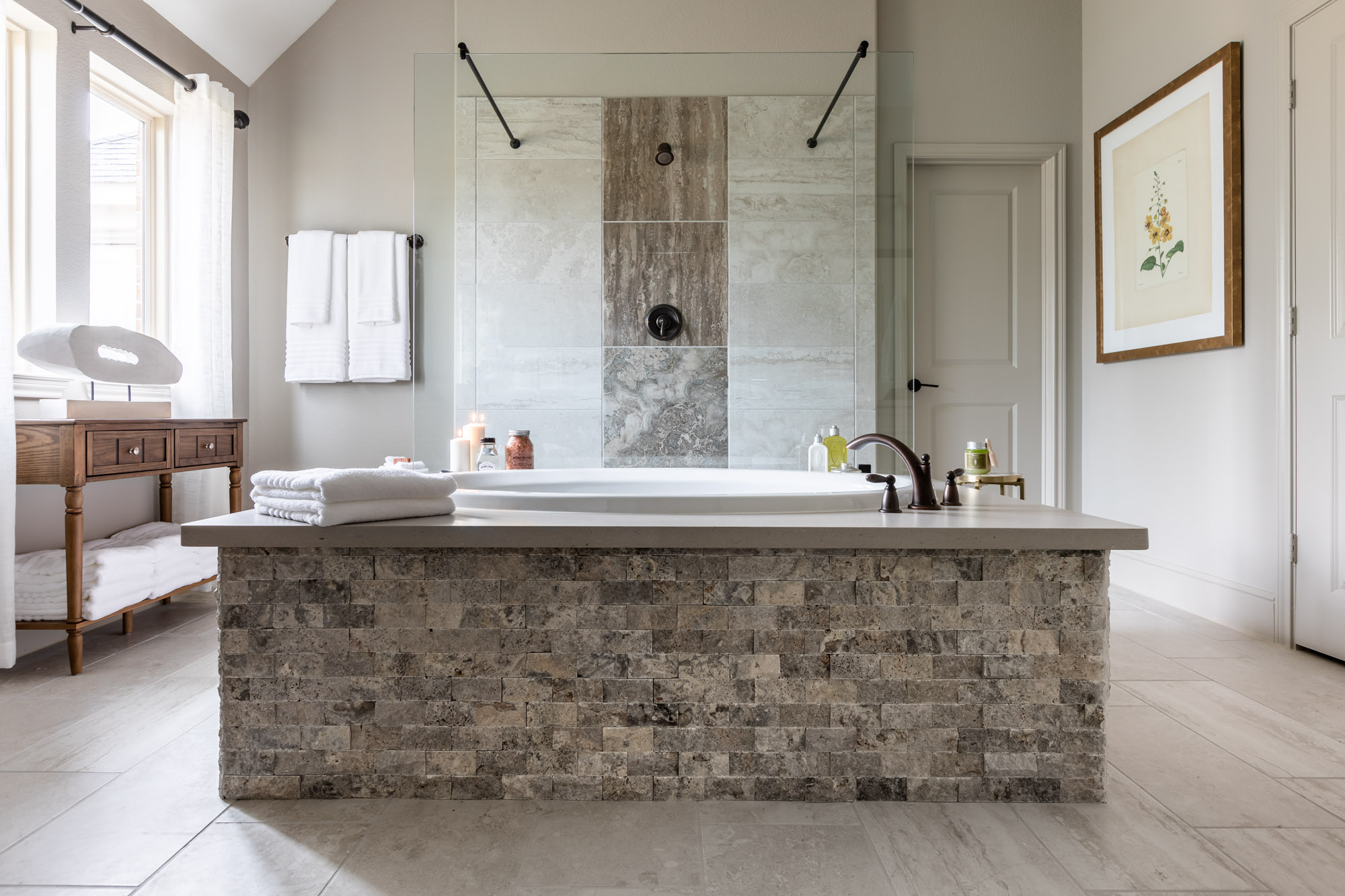 Harper's Preserve master bath with stone-covered bathtub in centre and shower with clear glass wall