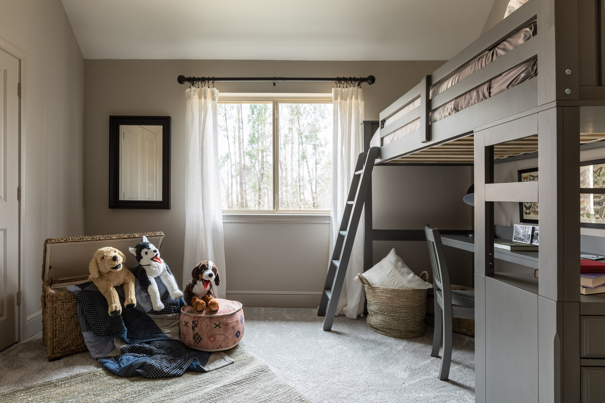 Harper's Preserve child's bedroom with bed elevated over desk and plush dog toys