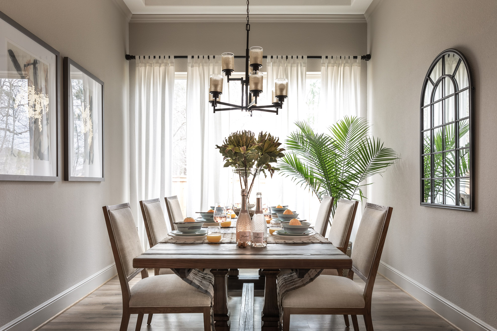 Harper's Preserve dining room with wood table, linen upholstered chairs, beige walls, and large plant