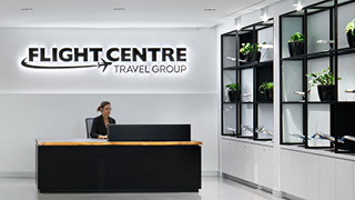 Flight Centre Vancouver reception area with black flight centre logo on white wall behind black reception desk