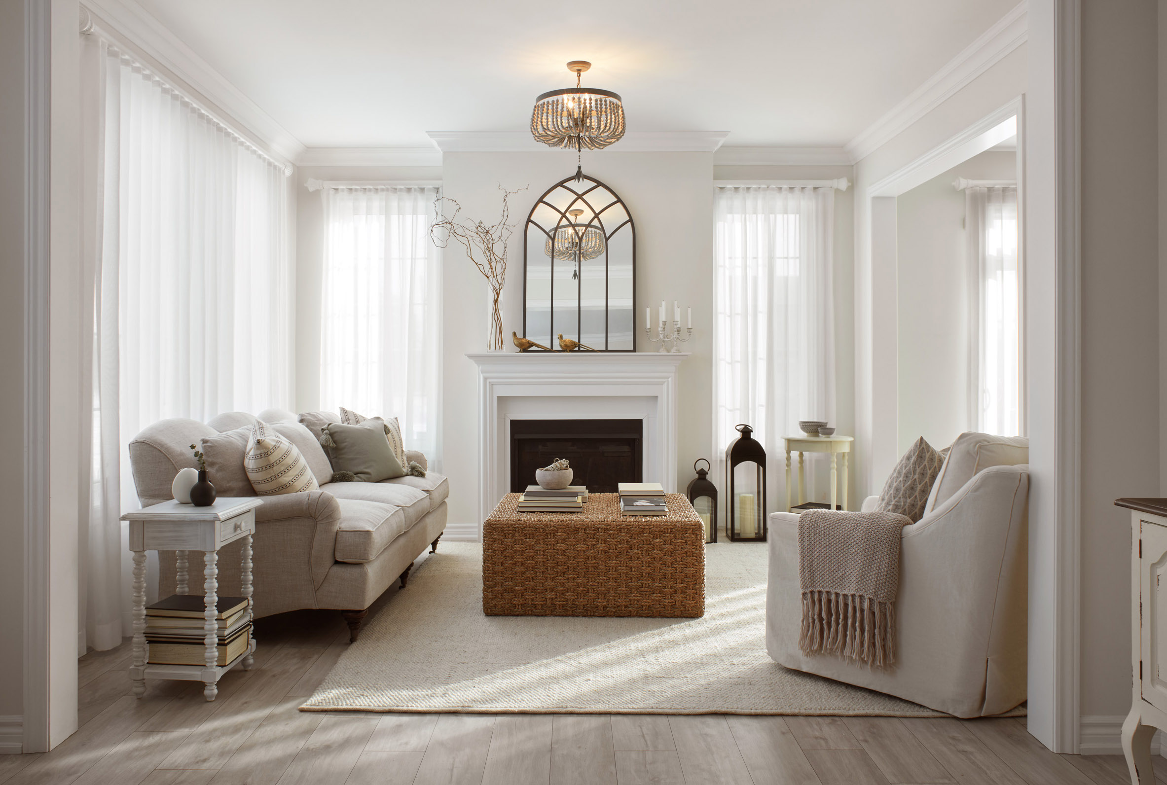 Shabby Chic living room with white walls and furniture, light wood floors, and large windows that let in sunlight.