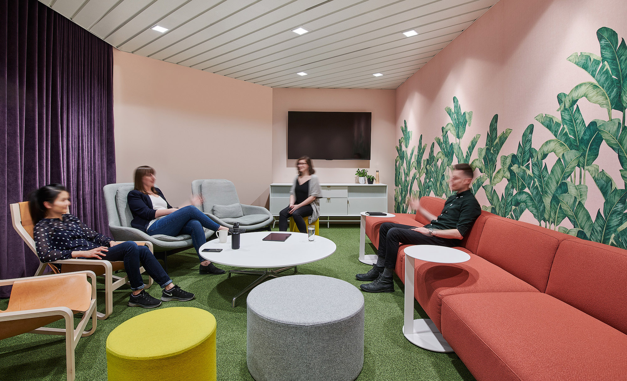 Mediabrands informal meeting room with pink walls, palm leaf graphics, and colourful residential-style furniture