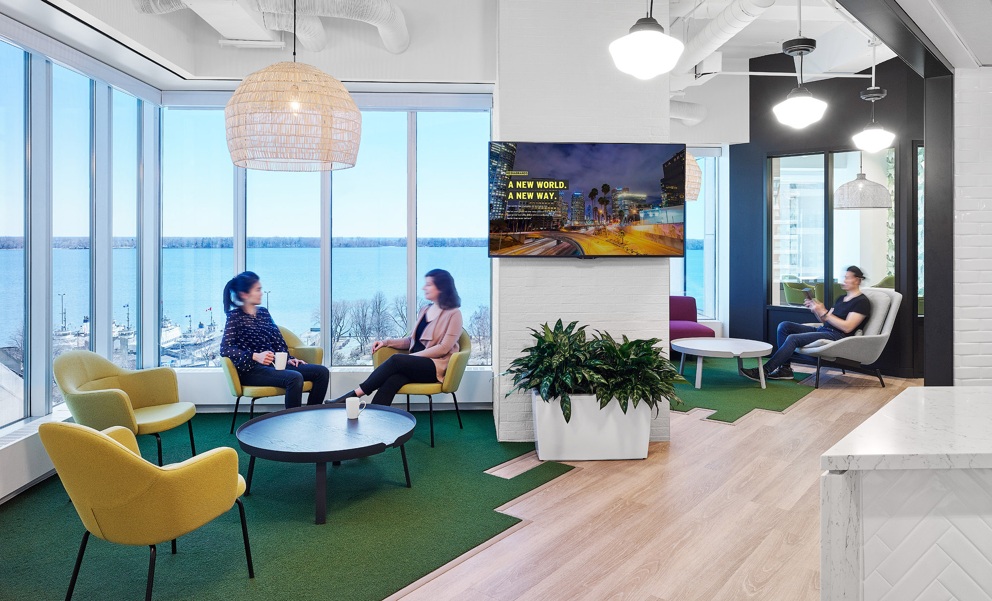 Mediabrands alcove in front of window with green turf, yellow armchairs, and domed bamboo light fixture