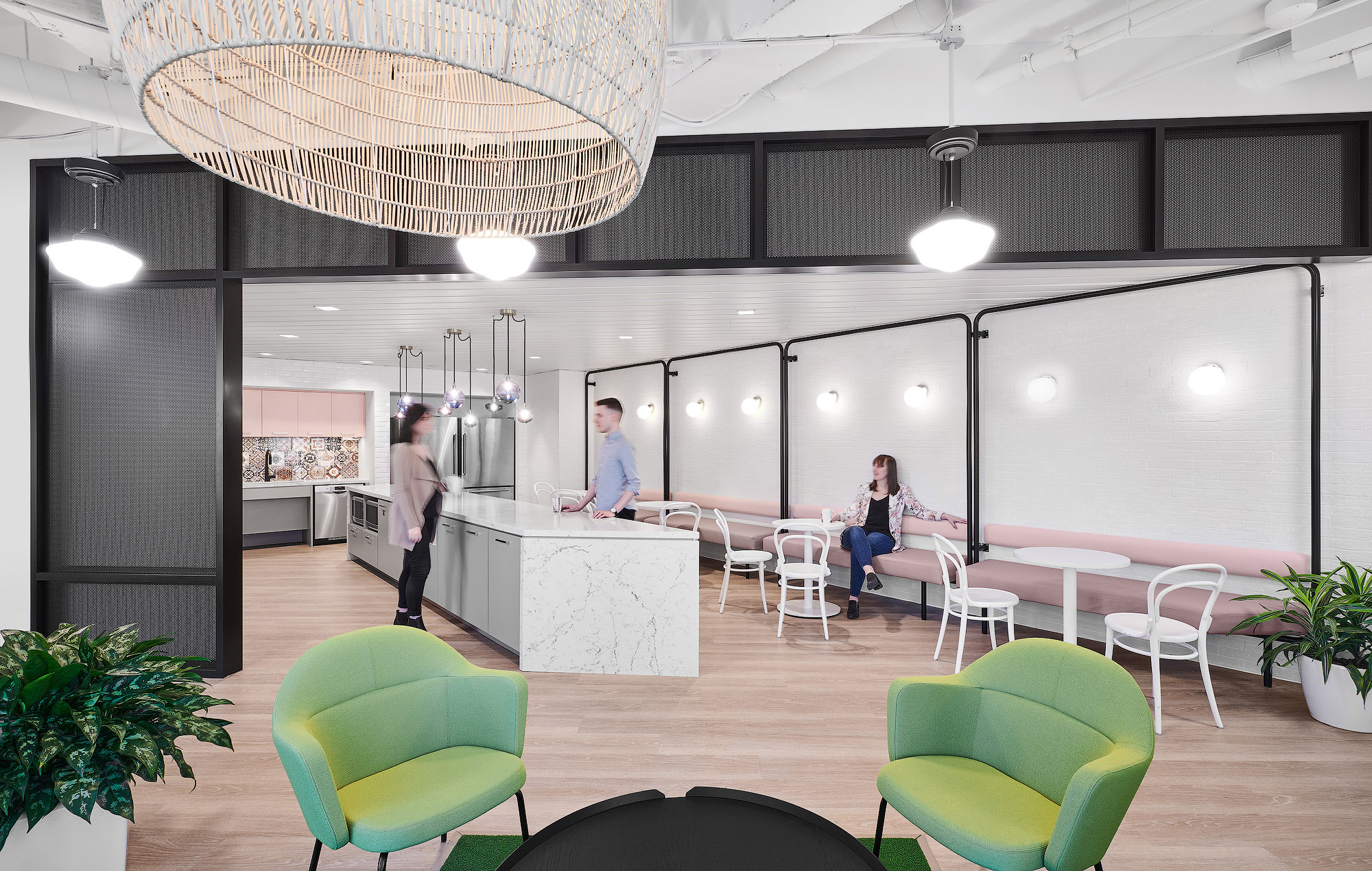 Mediabrands cafe with light wood floors, white brick walls, white marble island, and pink booth seating with white dining chairs