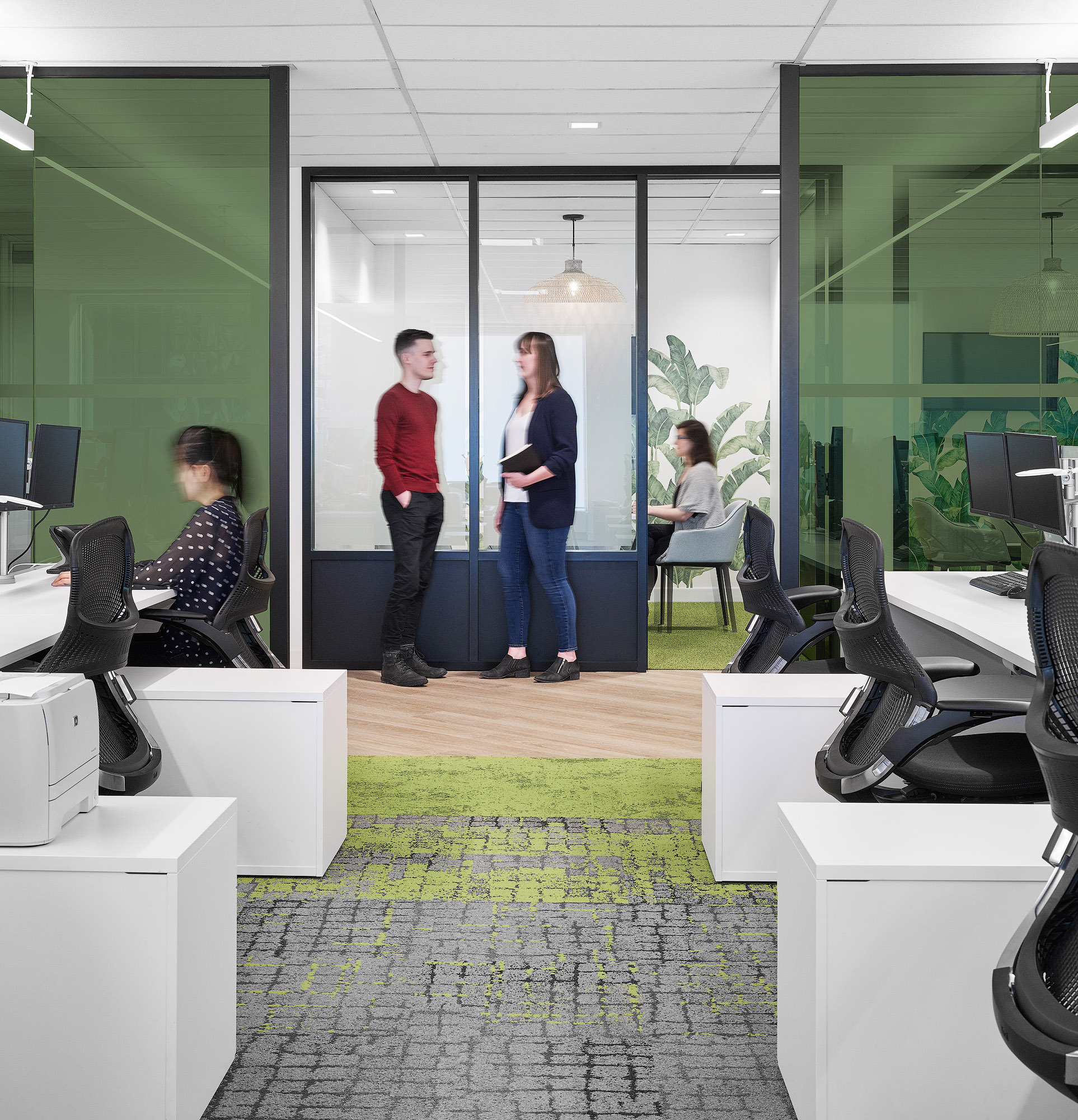 Mediabrands work stations with white desks, green and grey carpet, and green glass partitions
