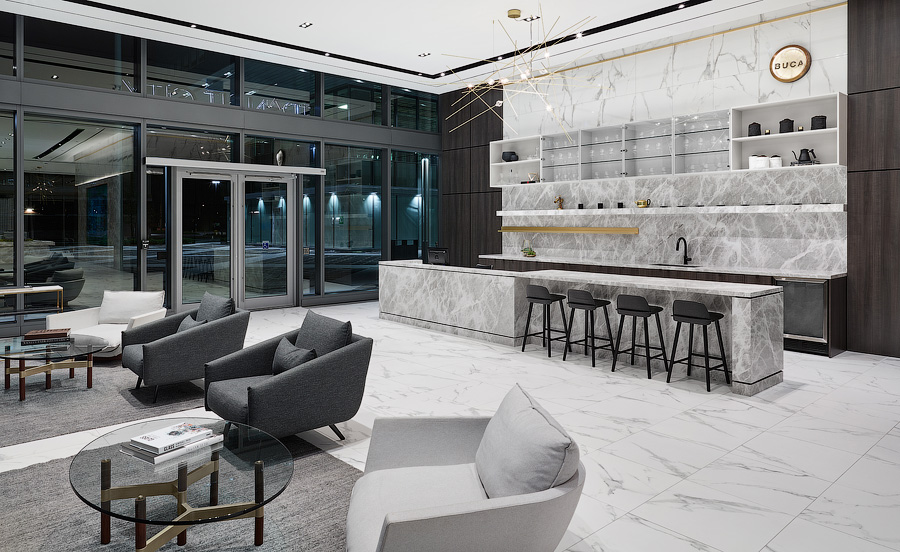 Transit City lobby with white marble floors, seating area, and Buca bar in background